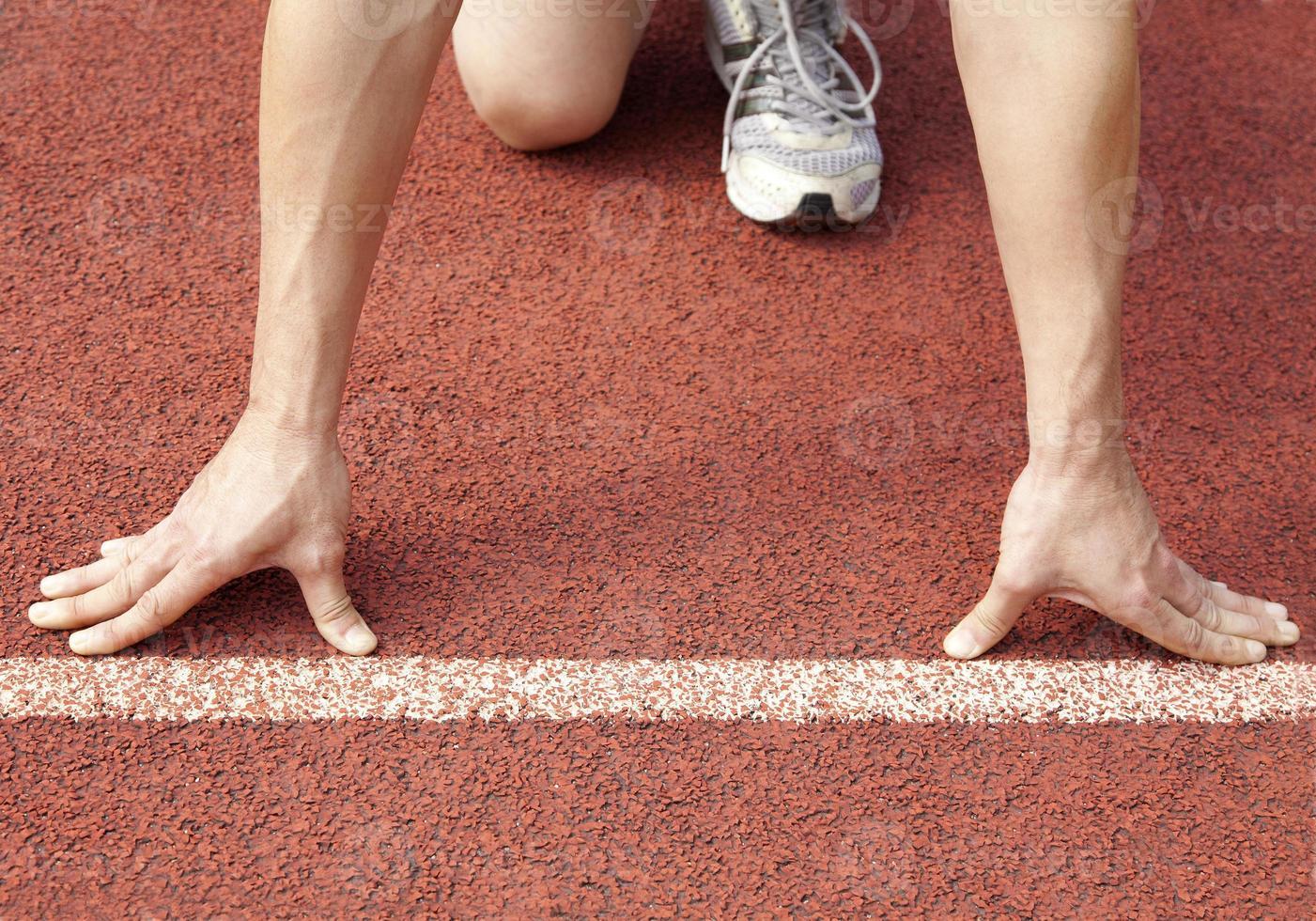 athlete at the start line of the stadium photo