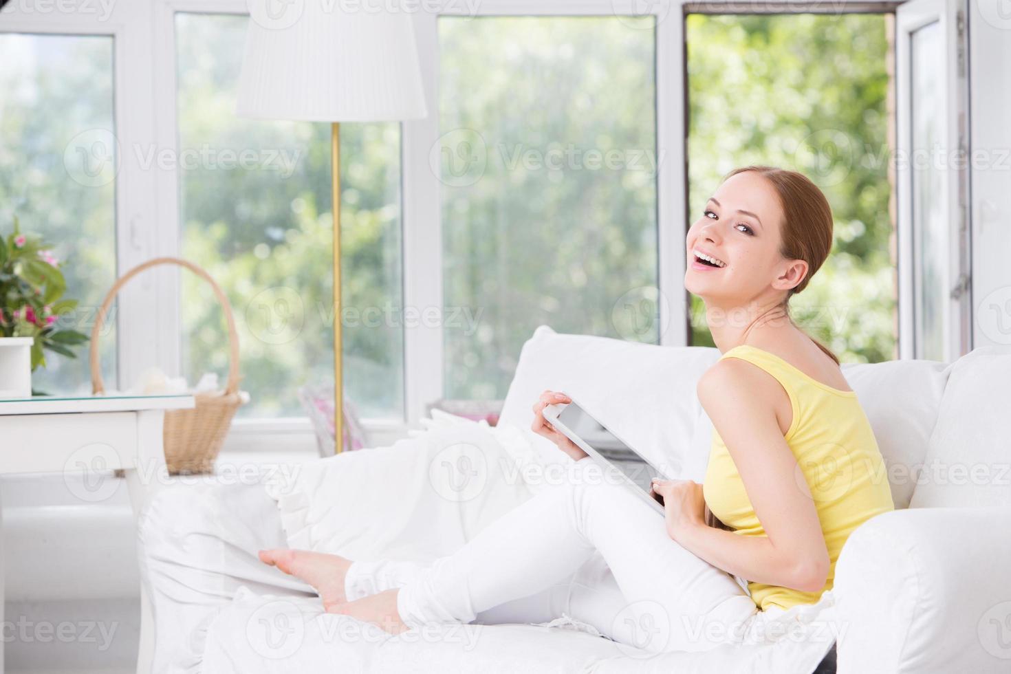 joven hermosa niña sentada en el sofá y muestra touchpad foto