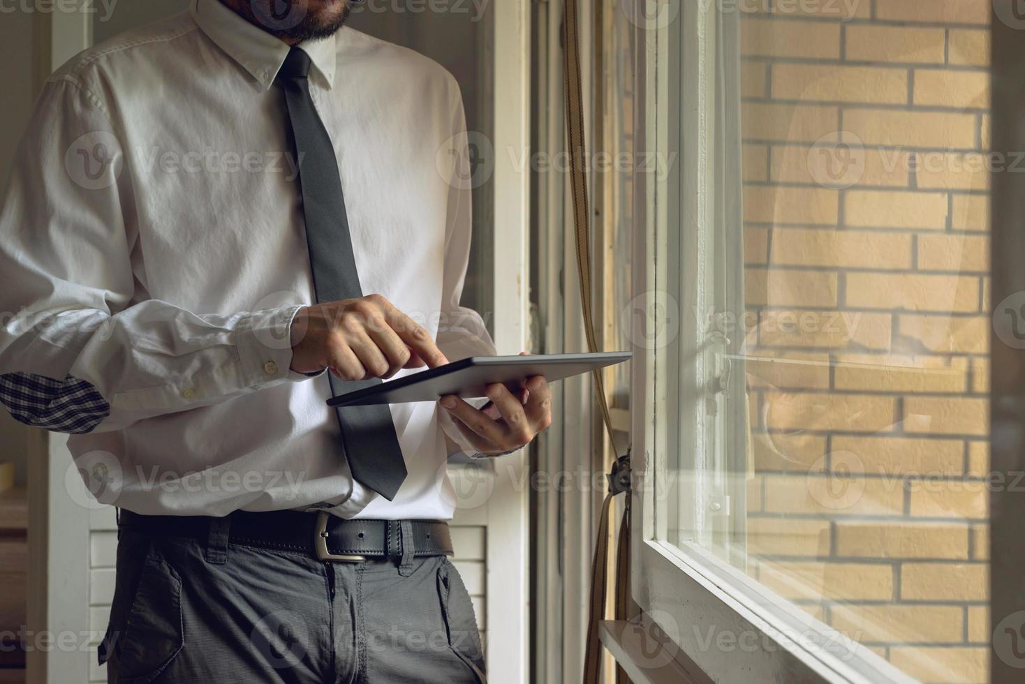Businessman taps digital tablet computer photo