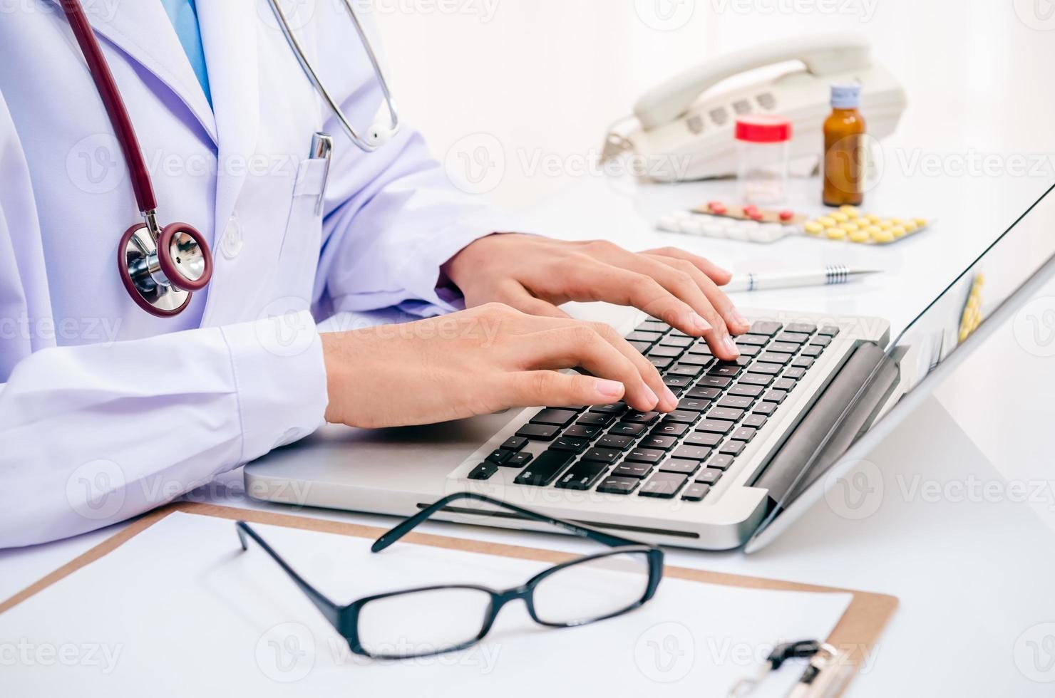 médico escribiendo en computadora foto