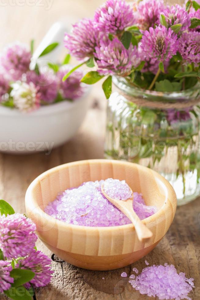 spa with purple herbal salt and clover flowers photo