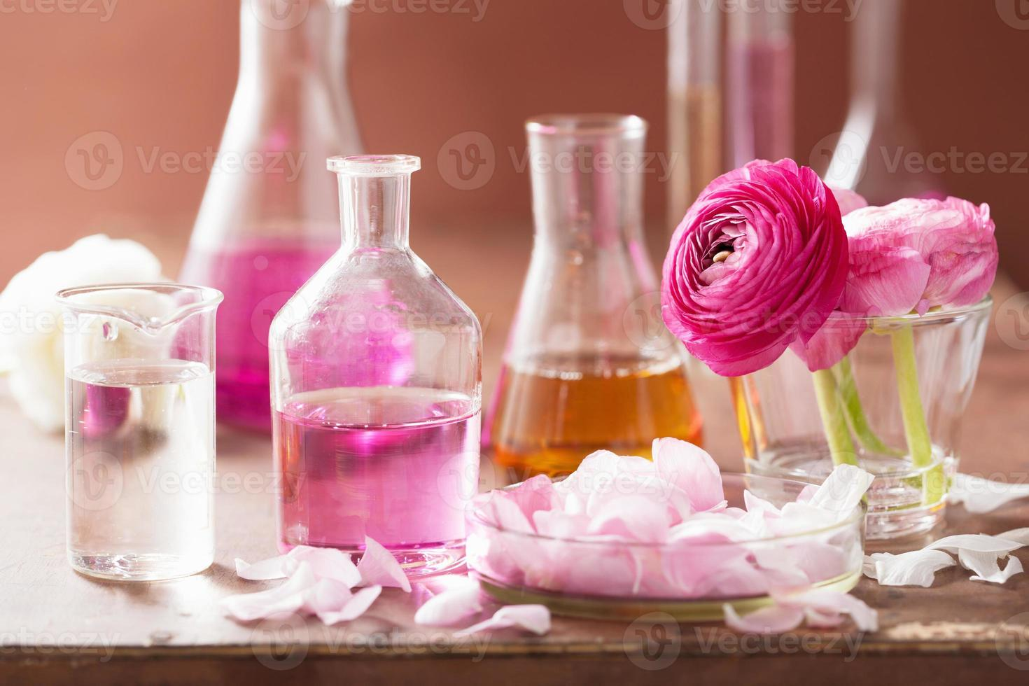 alchemy and aromatherapy set with ranunculus flowers flasks photo