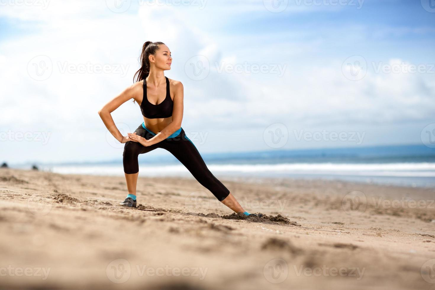 Fit woman  doing exercises for legs on the beach photo