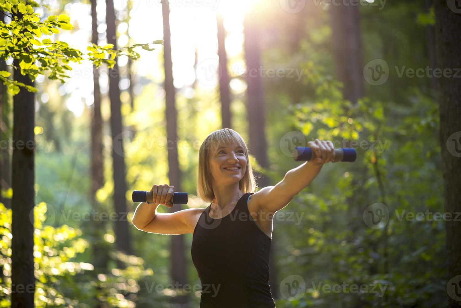 mujer joven trabajando con pesas foto