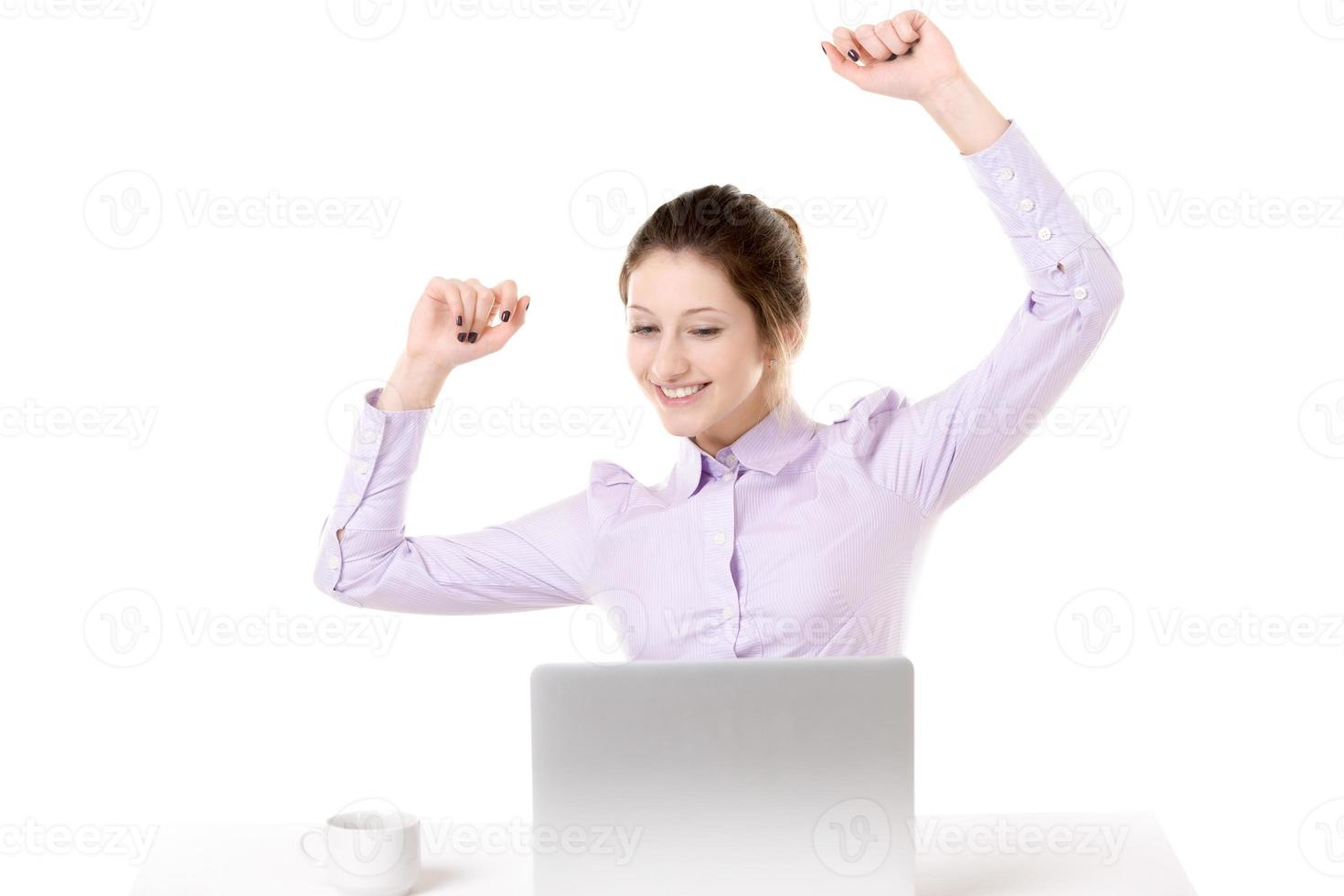 Young happy girl raising arms in front of laptop photo
