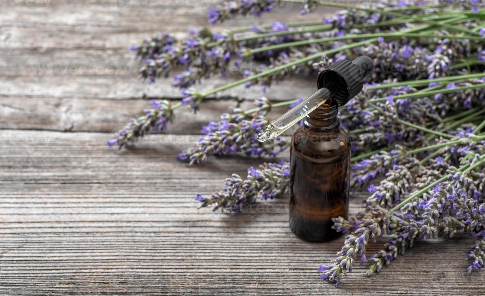 Herbal oil and lavender flowers bouquet on wooden background photo