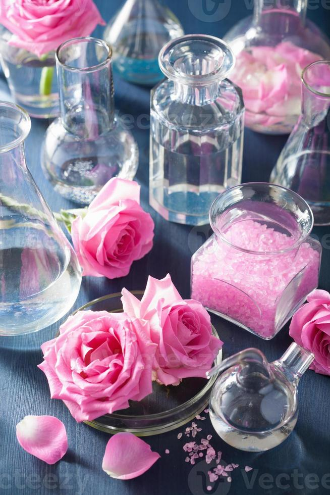 alchemy and aromatherapy with rose flowers and chemical flasks photo