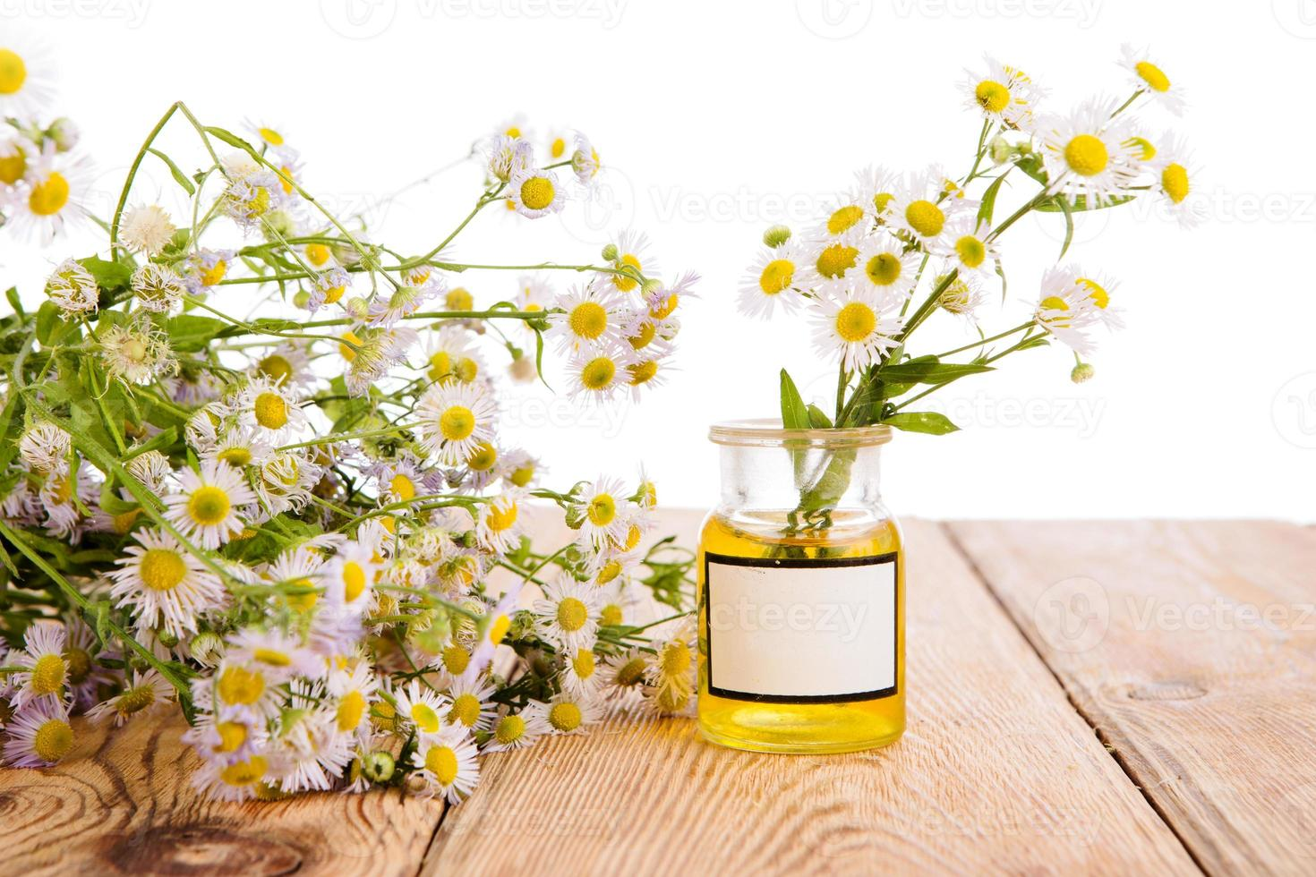 Alternative medicine concept - bottle with camomile on wooden ta photo