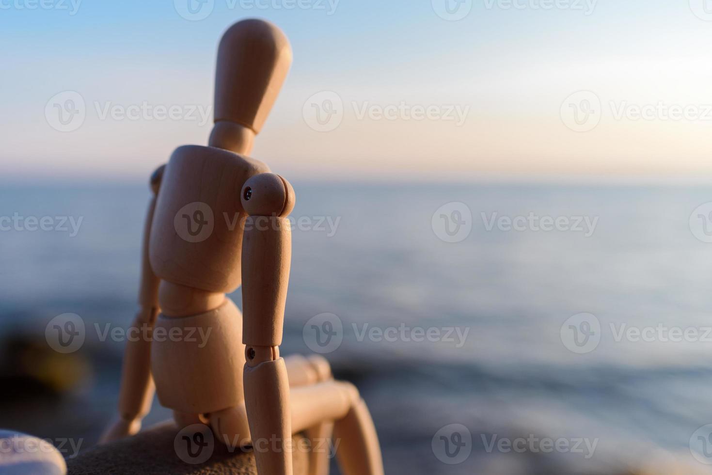 maniquí sentado en la piedra foto