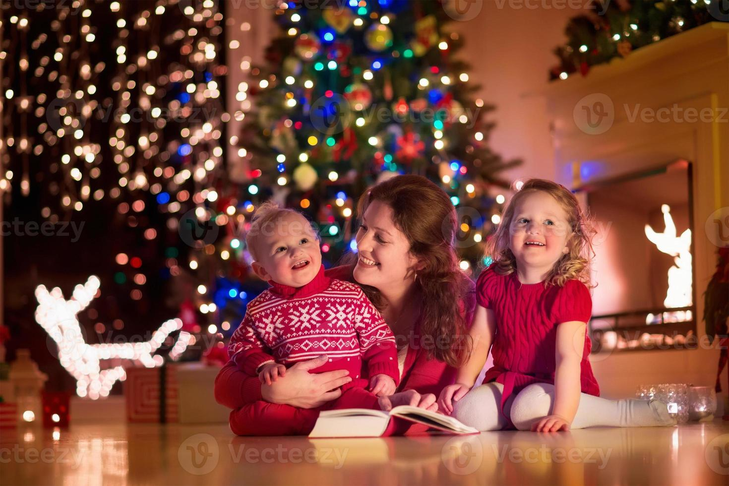 Mother and children at home on Christmas eve photo