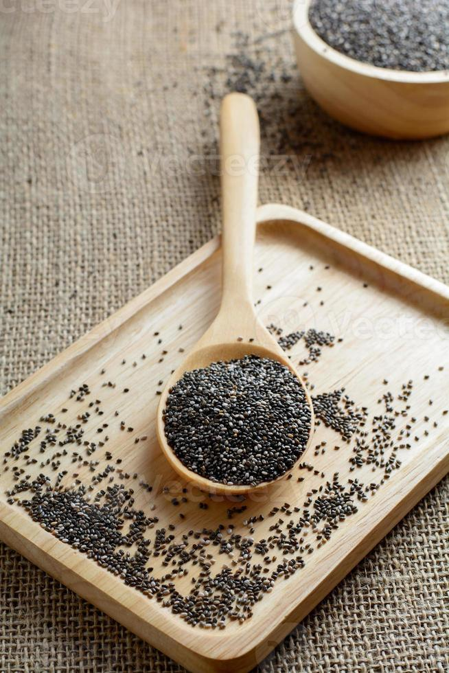 Chia seed on a wooden spoon against burlap background photo