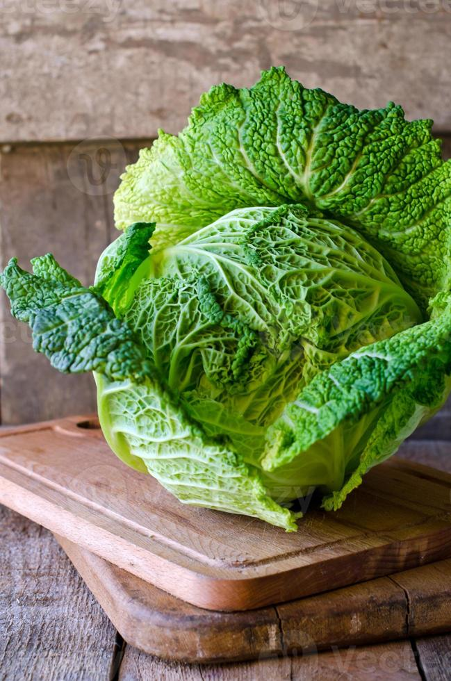 Fresh savoy cabbage on a wooden table photo