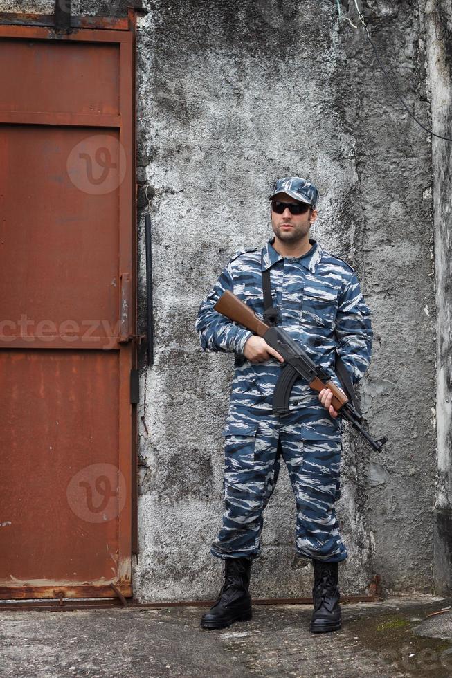 Hombre caucásico militar con rifle en guerra urbana foto