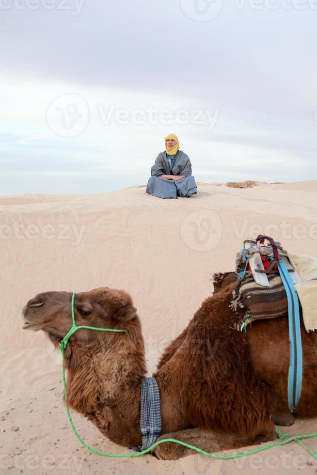 Caucasian man sitting on sand dune in desert with camel photo
