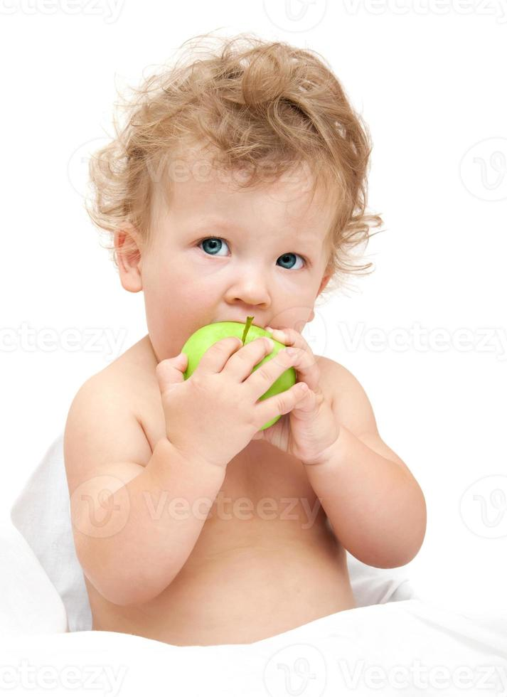 portrait of a child curly hair eats a green apple photo