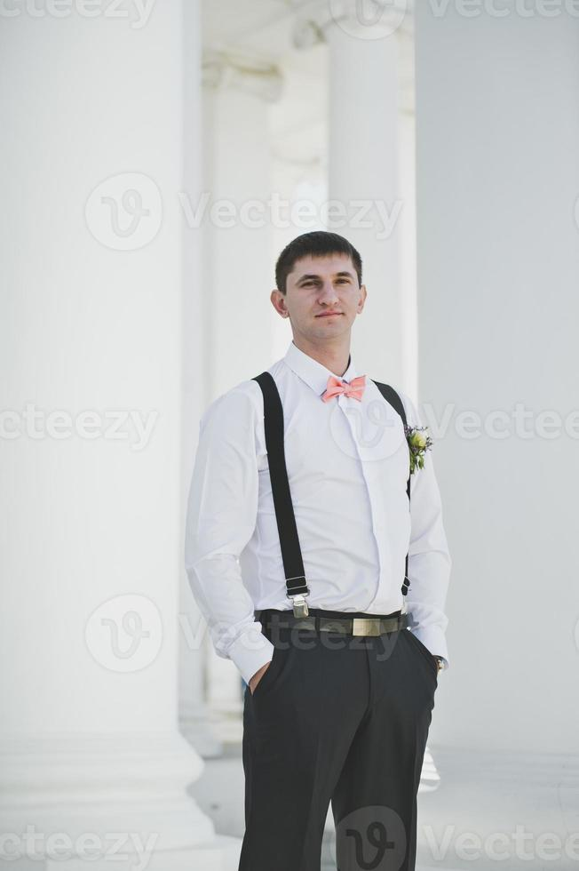 Groom on the background of white columns photo