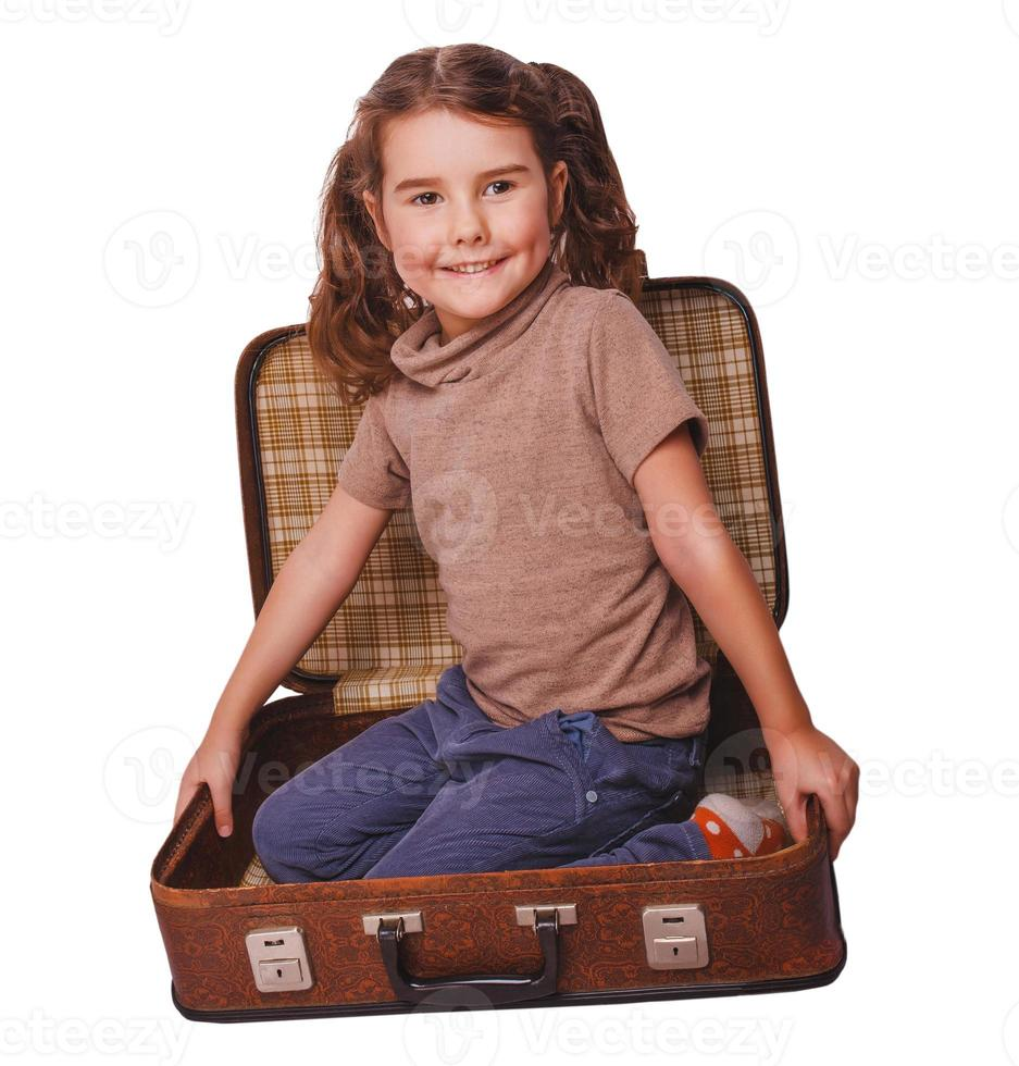girl baby brunette sitting in a suitcase for travel isolated photo
