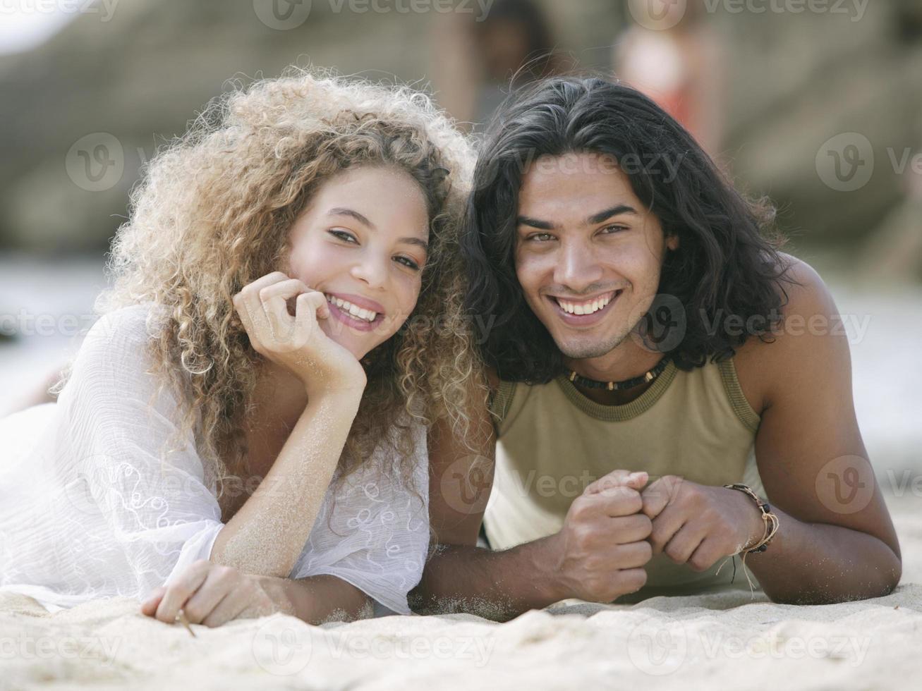 pareja joven tumbado en la playa y sonriendo foto