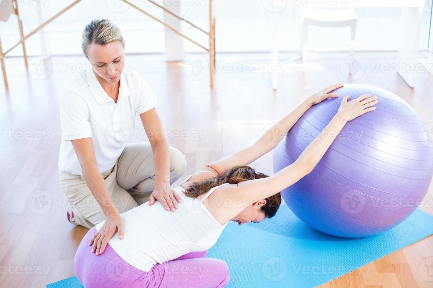 entrenador ayudando a mujer con pelota de ejercicios foto
