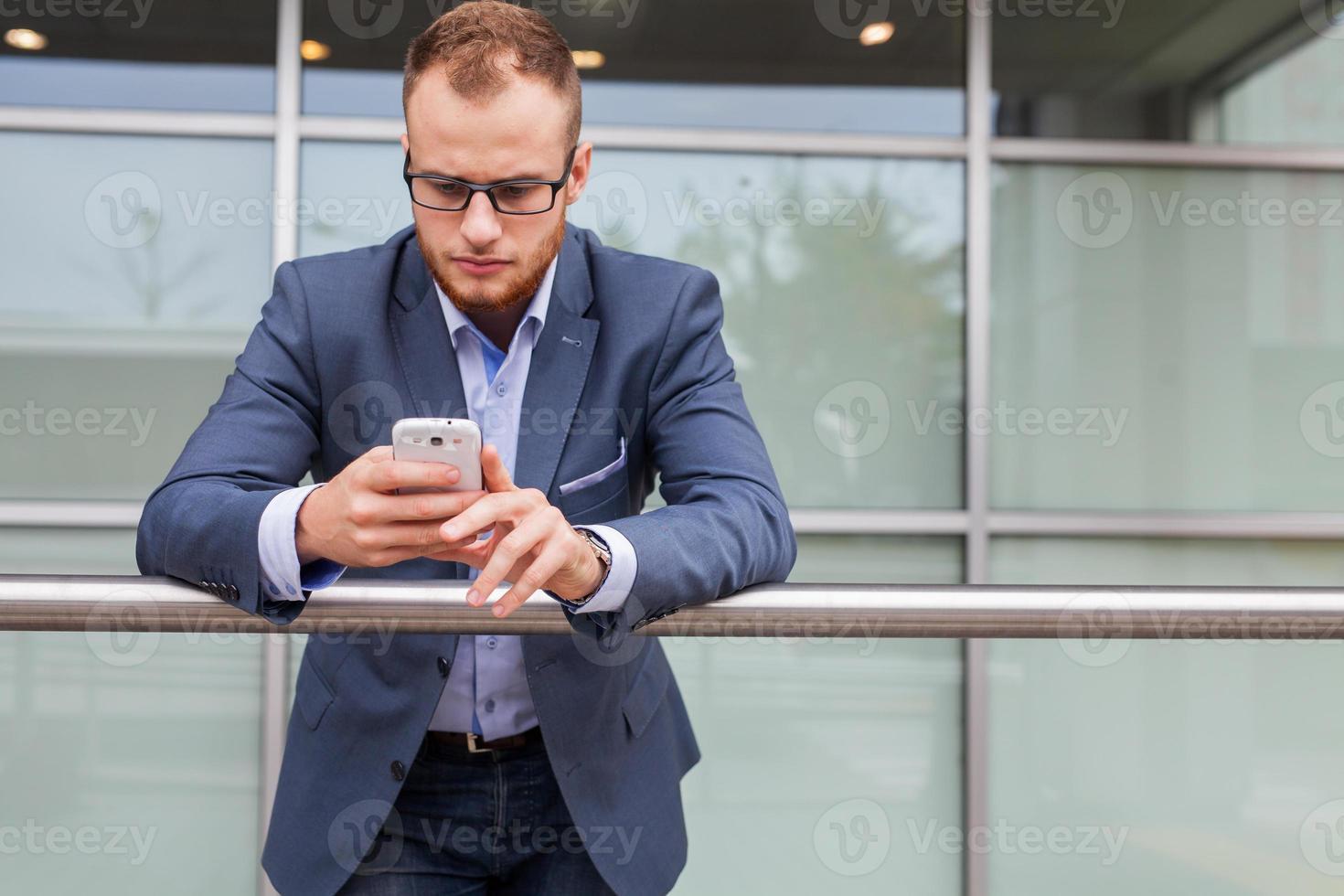 Hombre de negocios caucásico fuera de la oficina mediante teléfono móvil. foto