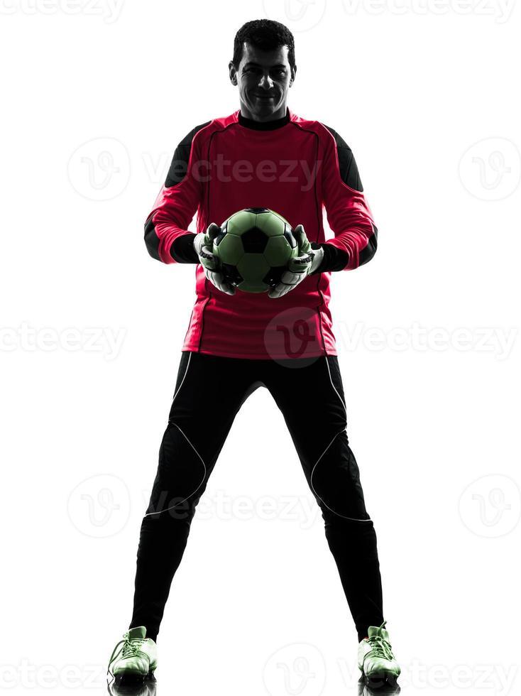 homem de goleiro de jogador de futebol caucasiano segurando a silhueta de bola foto
