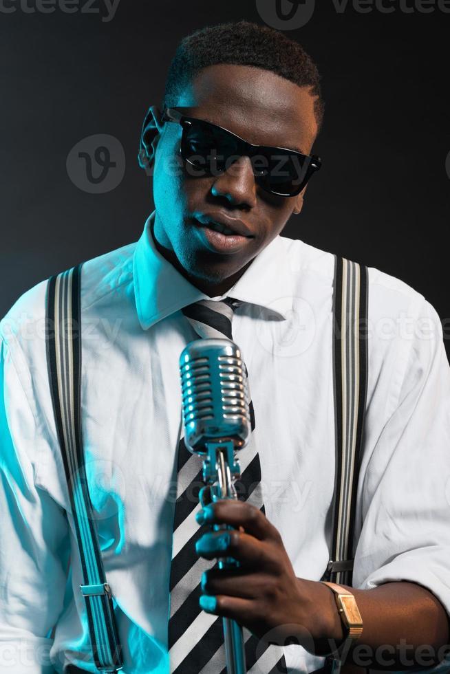cantante de jazz afroamericano retro con micrófono. foto