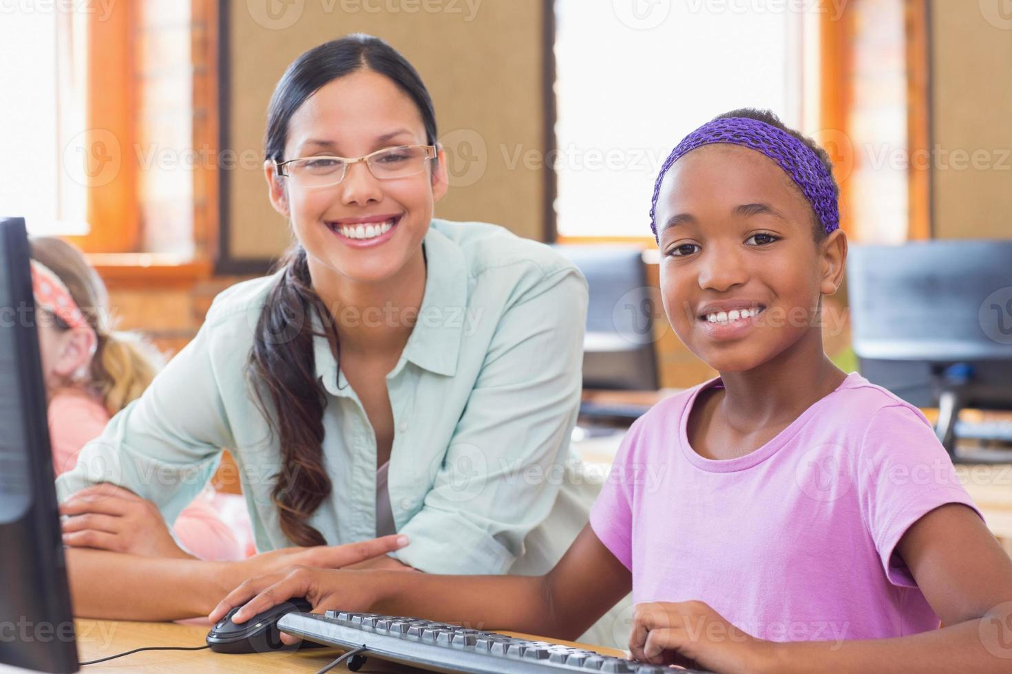 Cute pupil in computer class with teacher photo