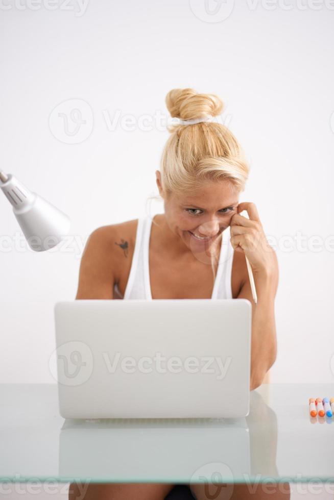 Mujer rubia usando su computadora portátil en su espacio de trabajo. vista frontal foto