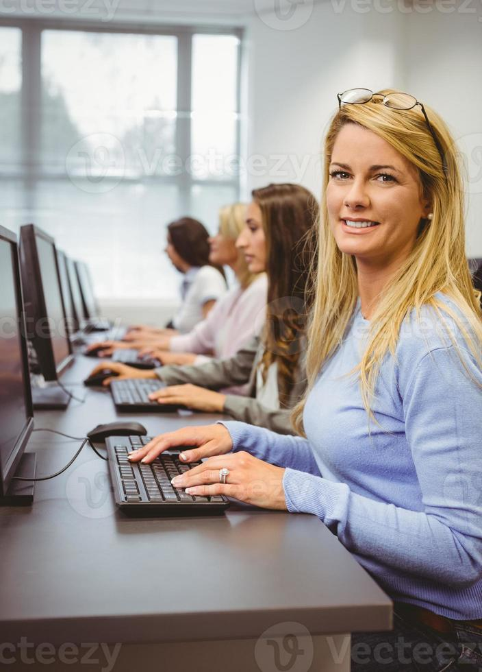 Happy woman in computer room smiling at camera photo