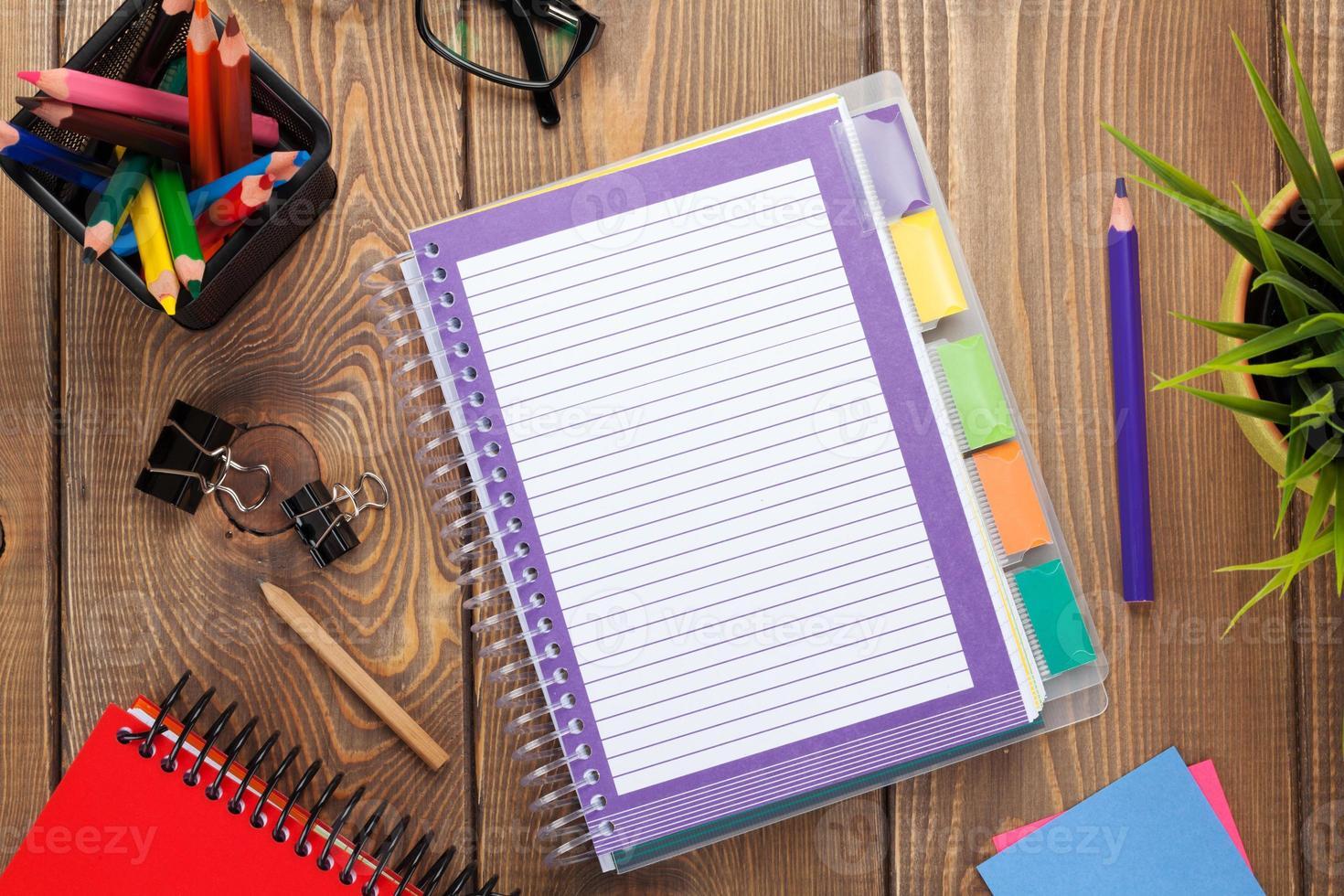 mesa de oficina con flores, bloc de notas en blanco y lápices de colores foto