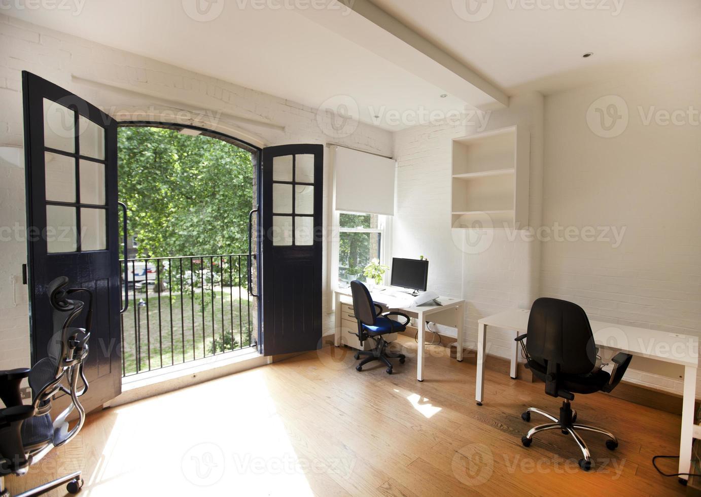 interior de oficina vacía con escritorios y sillas foto