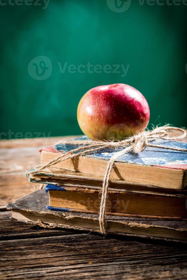 libros viejos y manzana en el pupitre foto