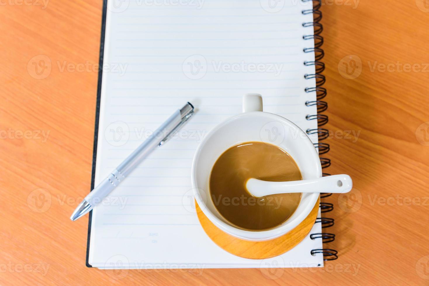 cuaderno y café sobre fondo de madera foto