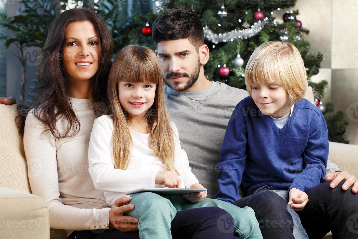 familia feliz en el árbol de navidad foto