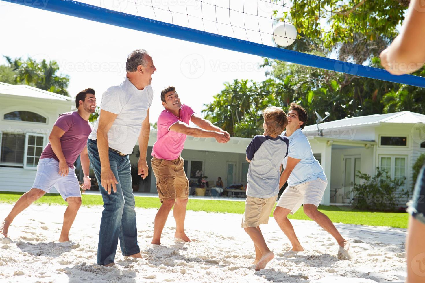 Familia multigeneración masculina jugando voleibol en el jardín foto
