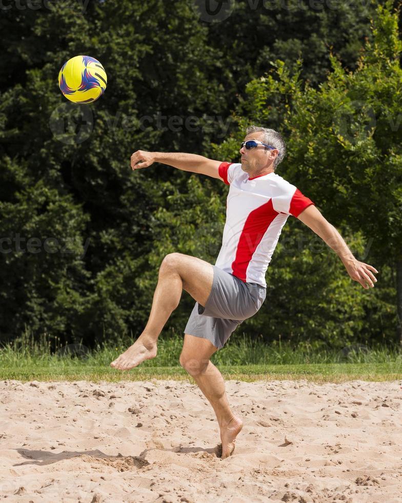 atleta jugando fútbol playa foto
