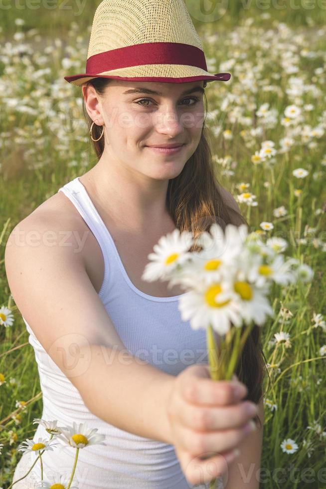 Beautiful woman enjoying daisy in a field photo