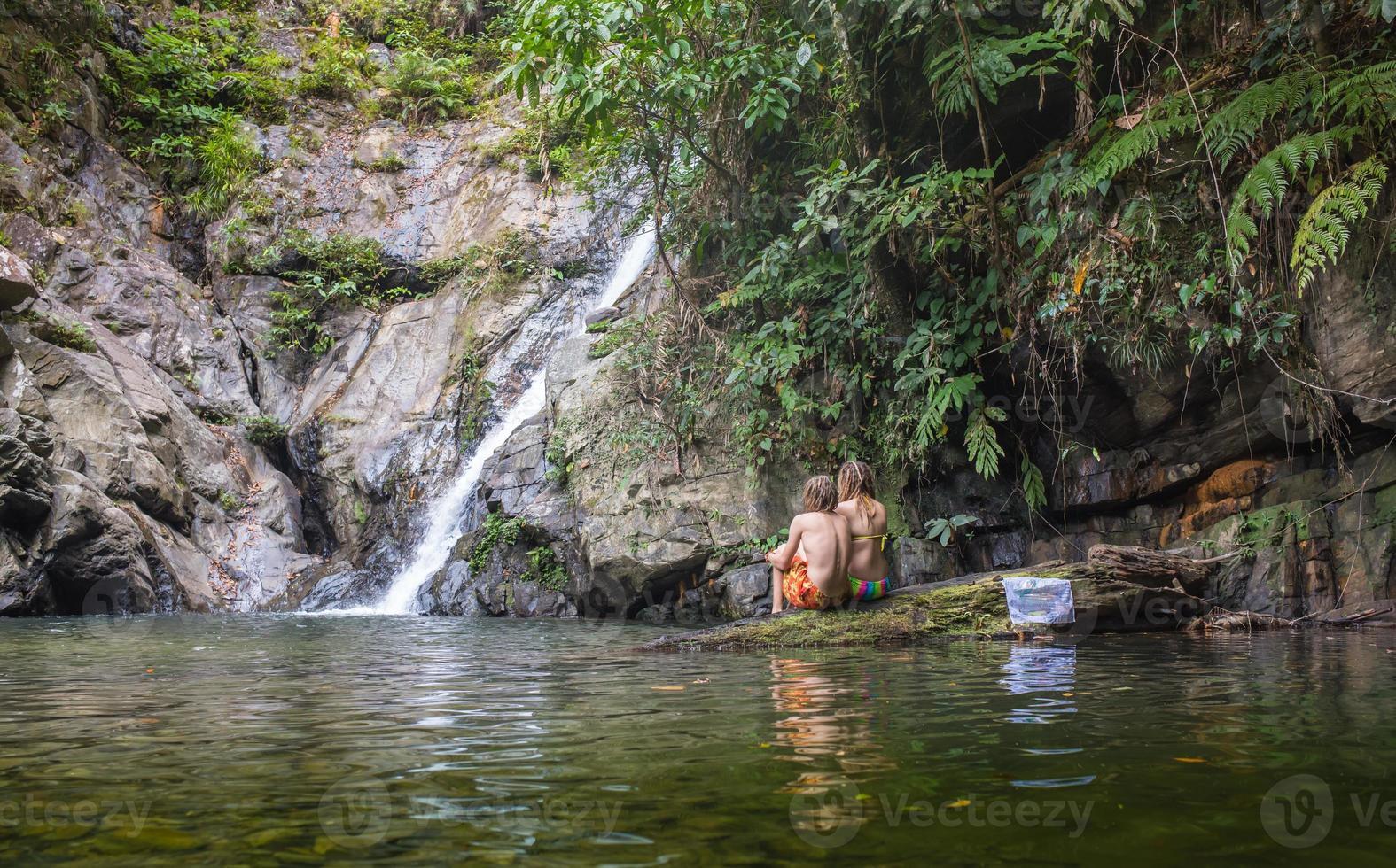 Pareja alegre disfrutando del baño del río por la cascada foto