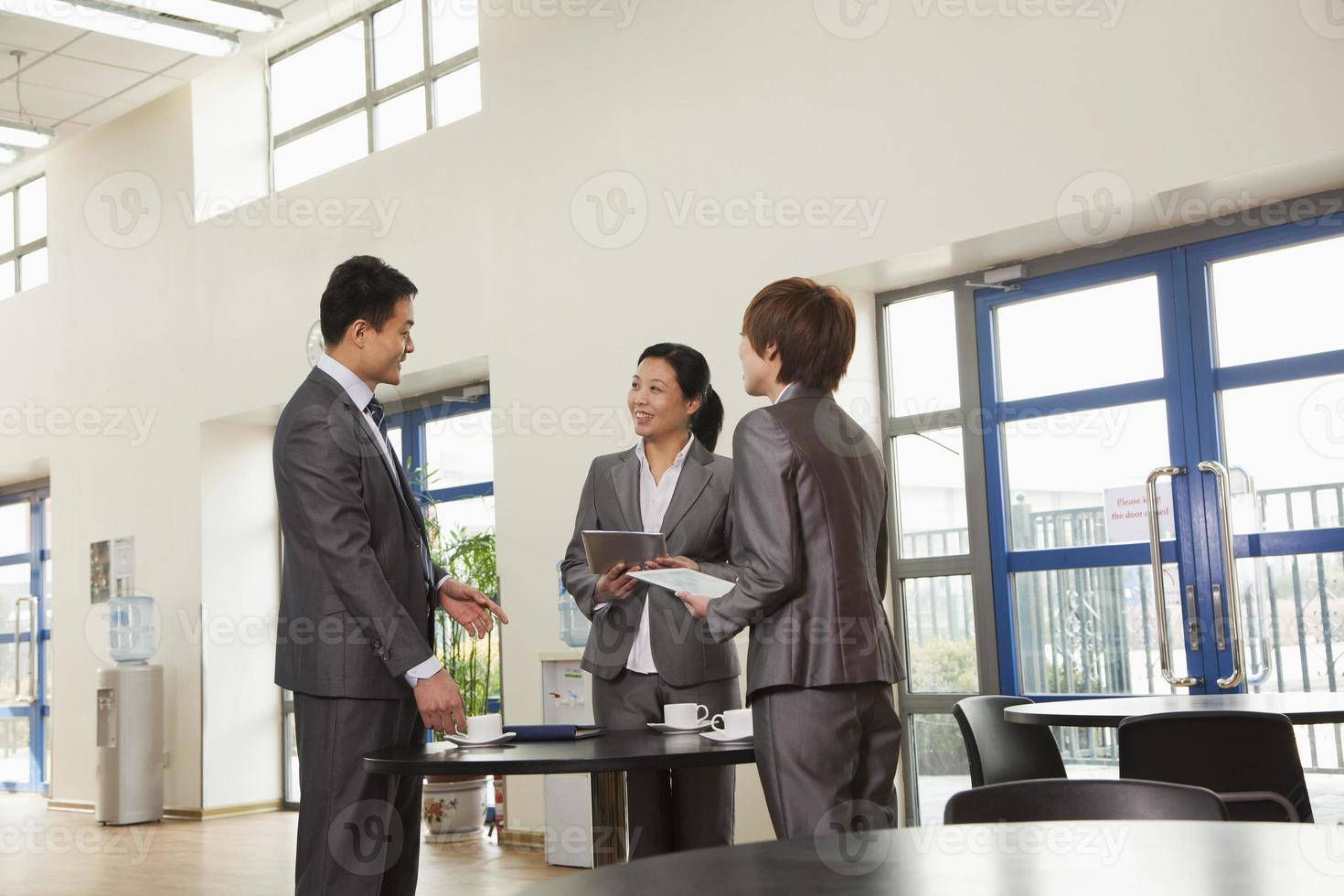 Three business people meeting in company cafeteria photo