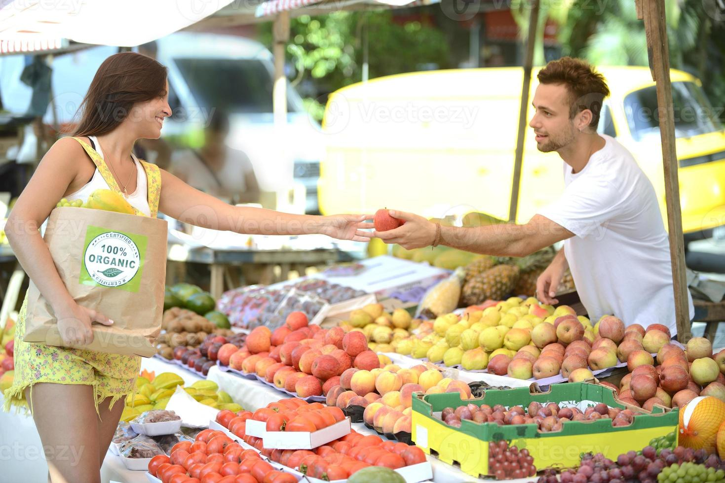 Greengrocer handing out a fruit to a consumer. photo