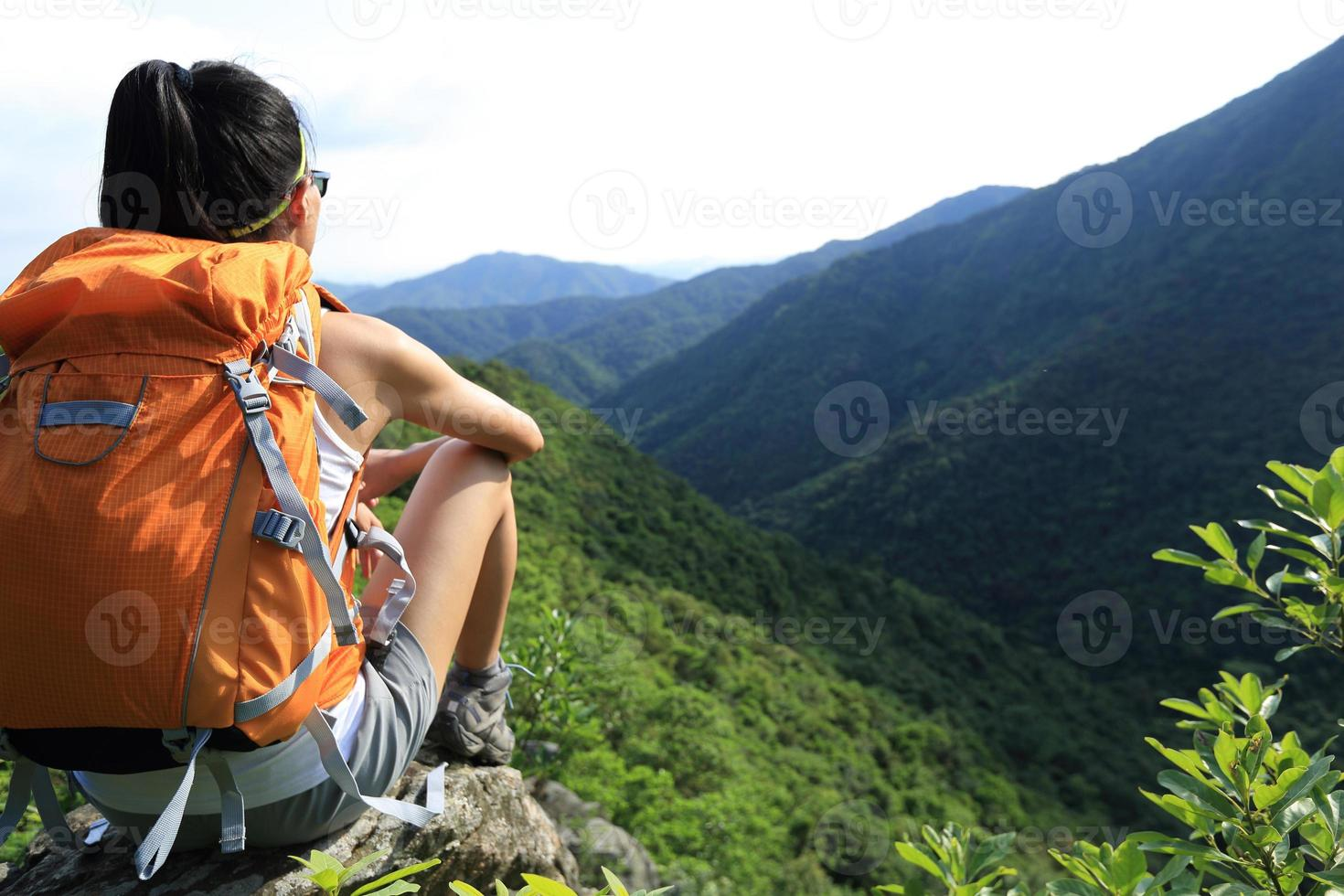 mujer mochilero disfrutar de la vista en el acantilado de pico de montaña foto
