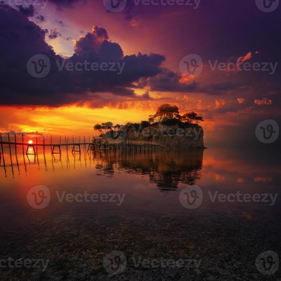 belo pôr do sol com ilha rochosa foto