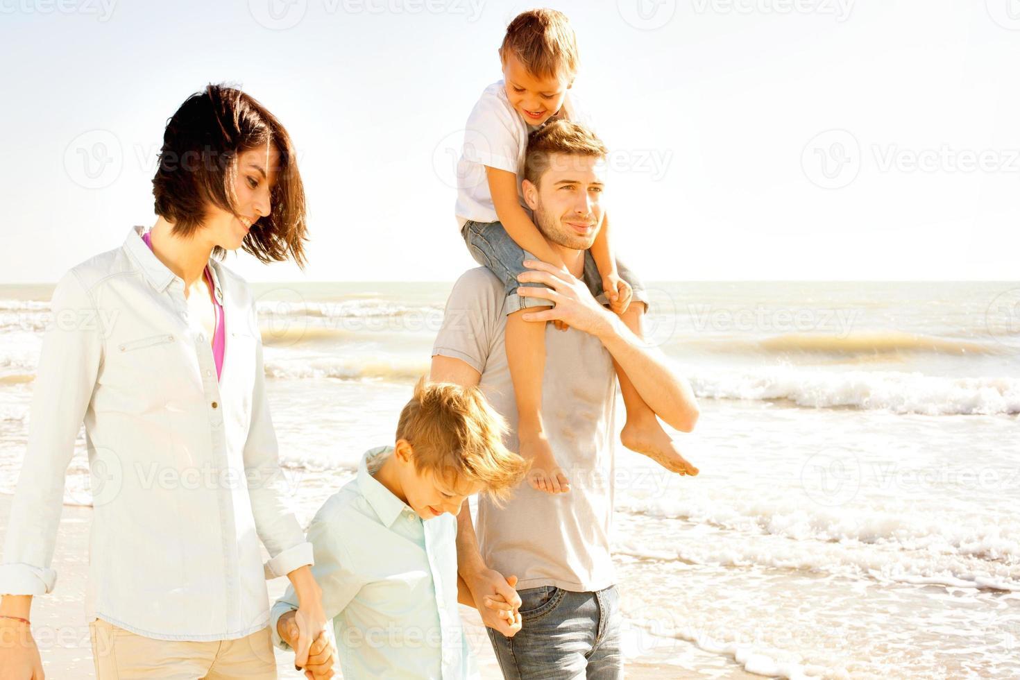 familia disfrutaba caminando en la playa en el mar foto