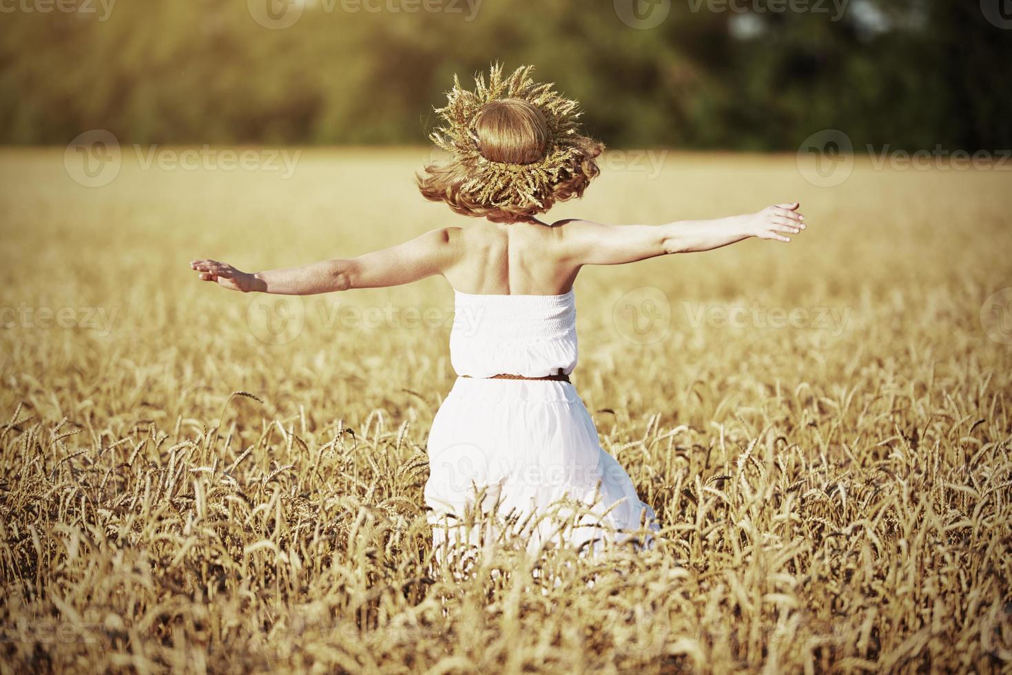 niña feliz disfrutando de la vida en el campo de trigo en verano foto