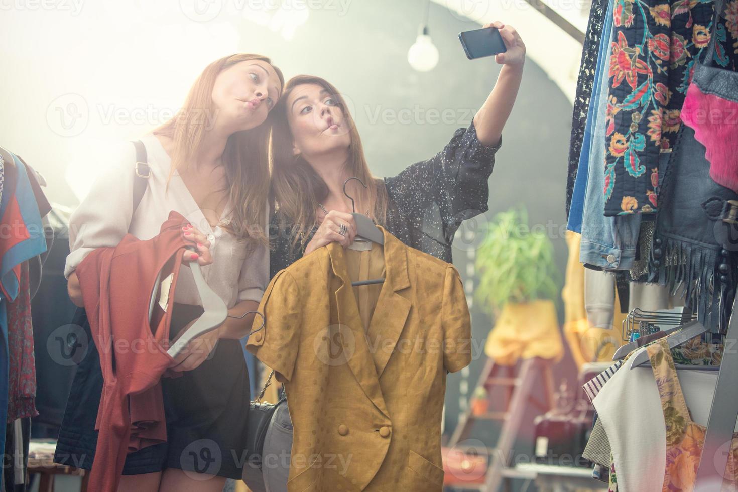 jóvenes amigas rubias y marrones disfrutan en una tienda de ropa de segunda mano foto