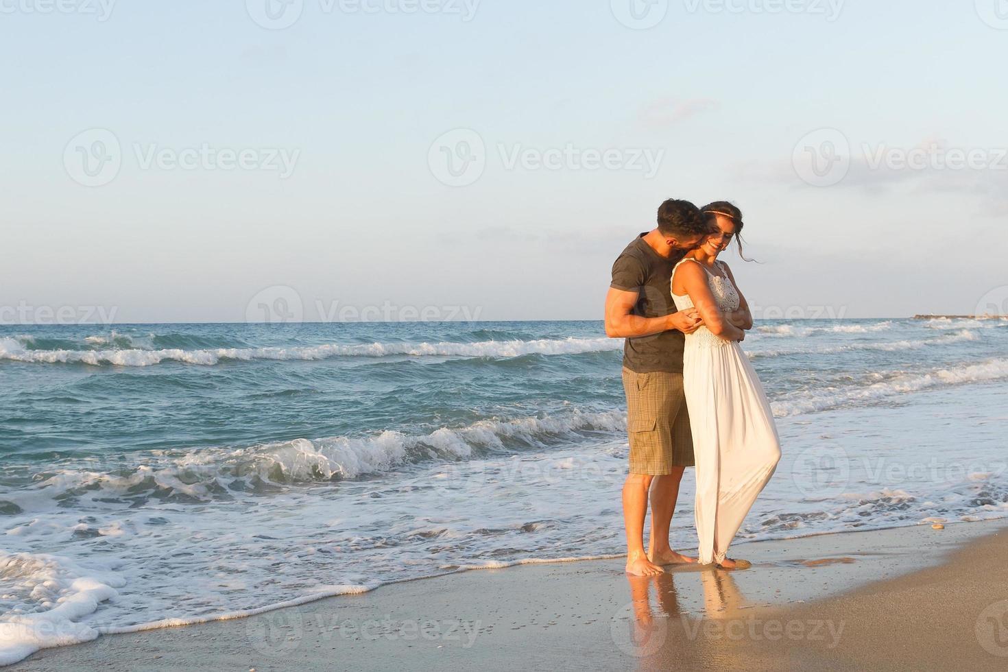joven pareja disfruta caminando en una playa nublada al anochecer foto