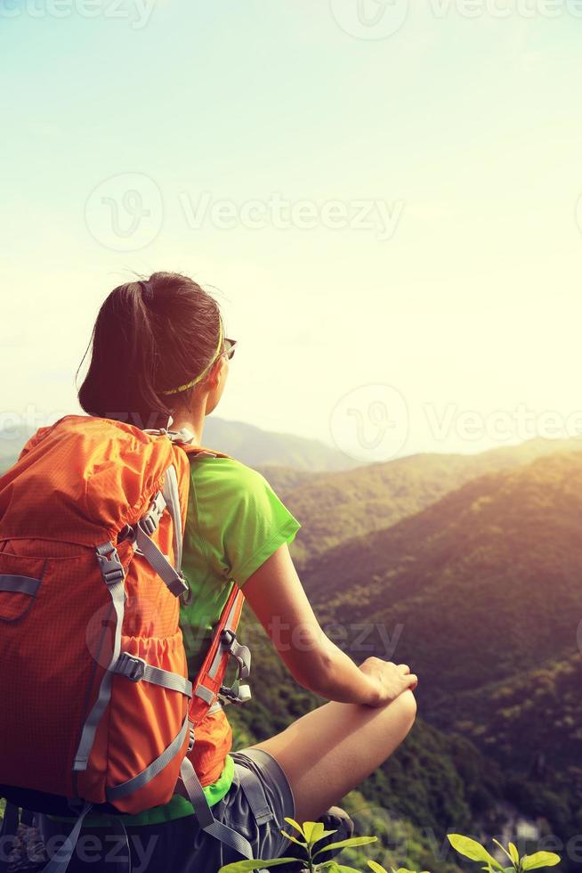 woman backpacker enjoy the view at mountain peak cliff photo
