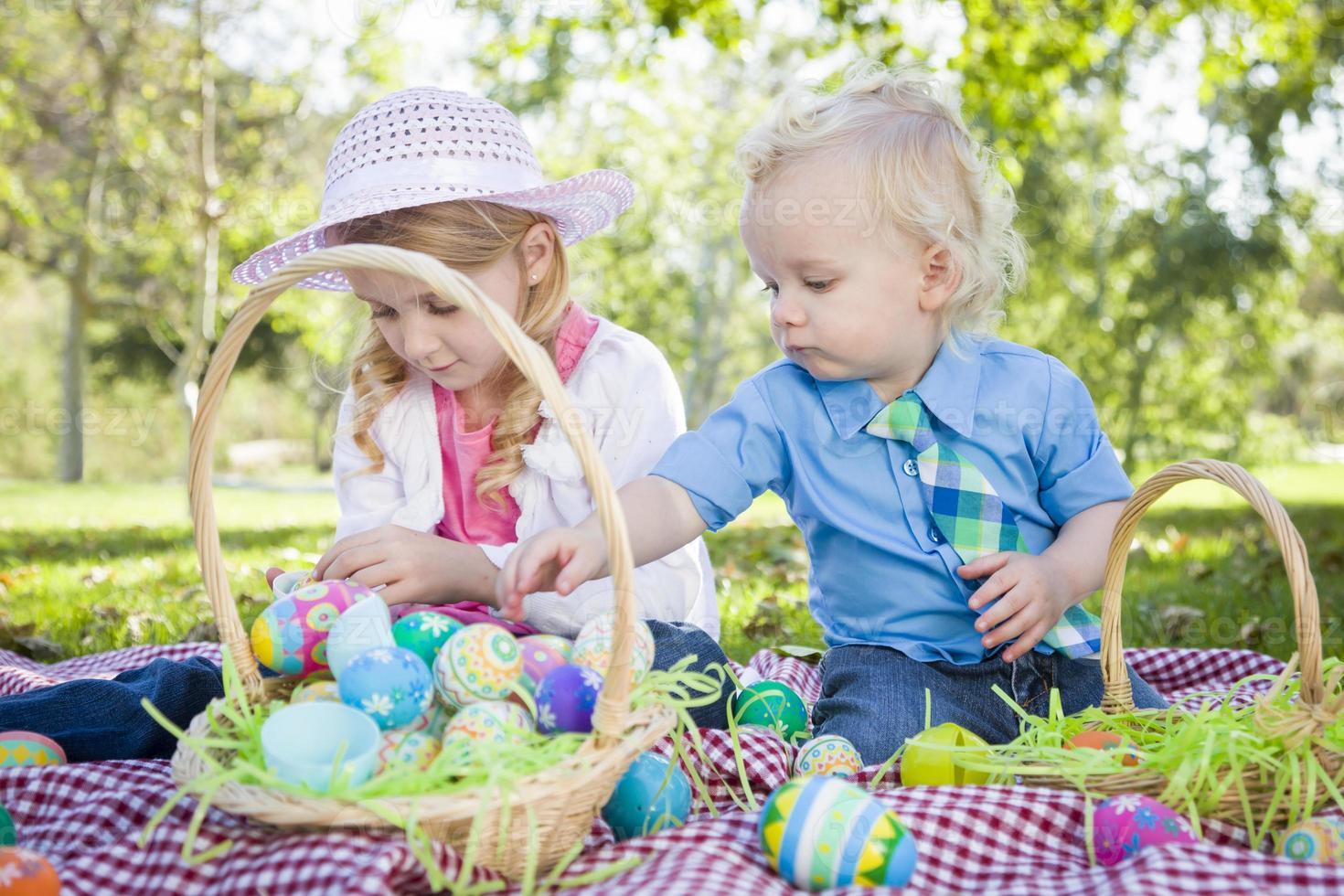 lindo joven hermano y hermana disfrutando de sus huevos de pascua afuera foto
