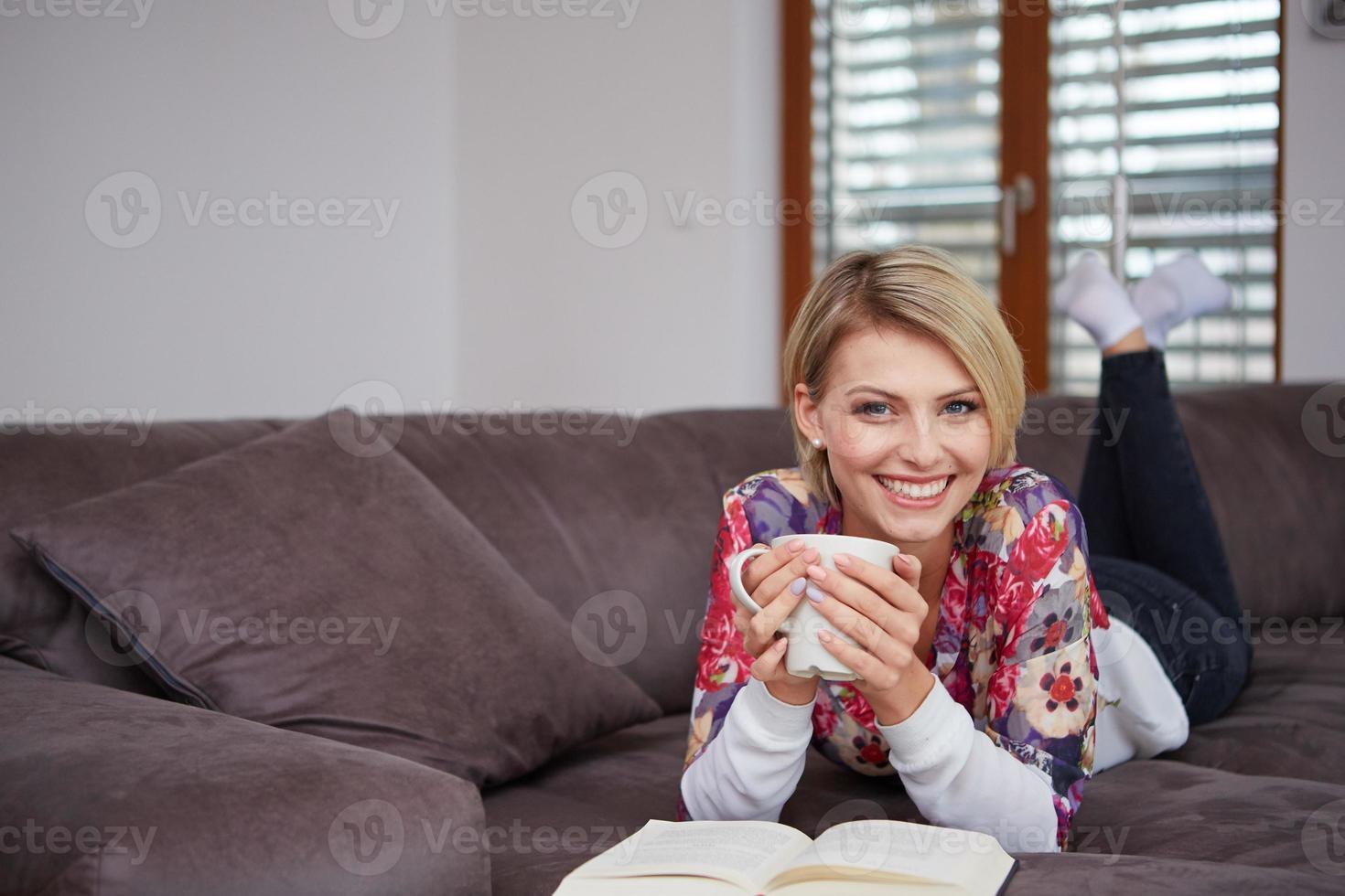 Mujer disfrutando leyendo un libro en casa tumbado en el foto