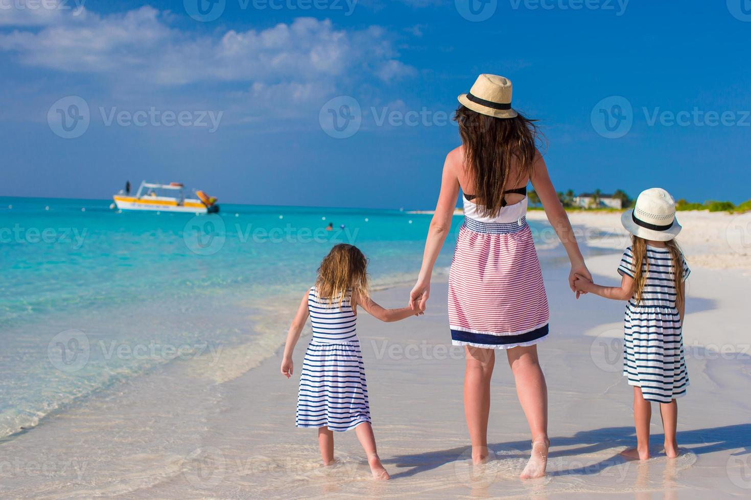 Back view of mother and little daughters enjoy summer vacation photo